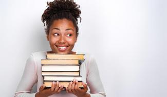 student holding a stack of books
